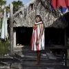 Andres, 39 years old Tida Wena in a traditional warao dress beside his home. Ironically the origin of this dresses is owing to capuchin monks who designed and spread them among the indians who were used to be half-naked.